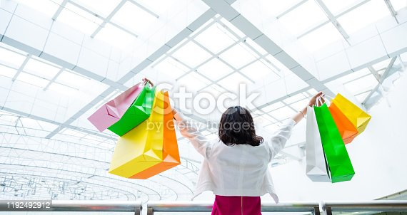 Young female shopper holding colorful shopping bags with her arms outstretched at mall.