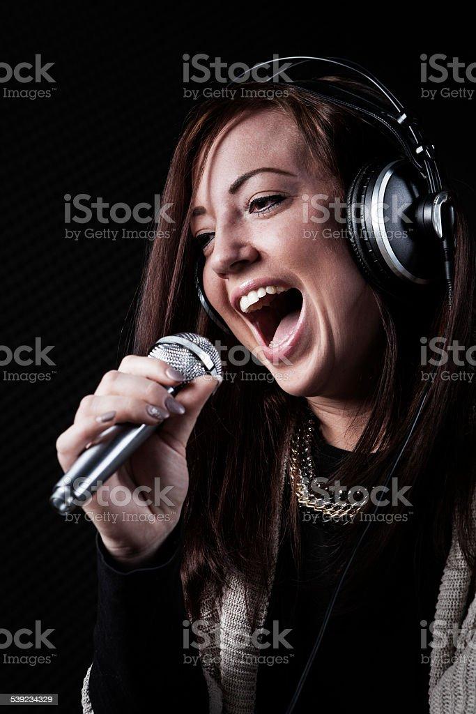 Jovem cantora apresentam no estúdio de gravação de áudio foto royalty-free