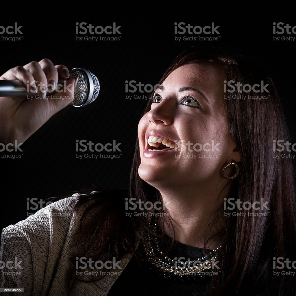 Young female singer performing at sound recording studio royalty-free stock photo