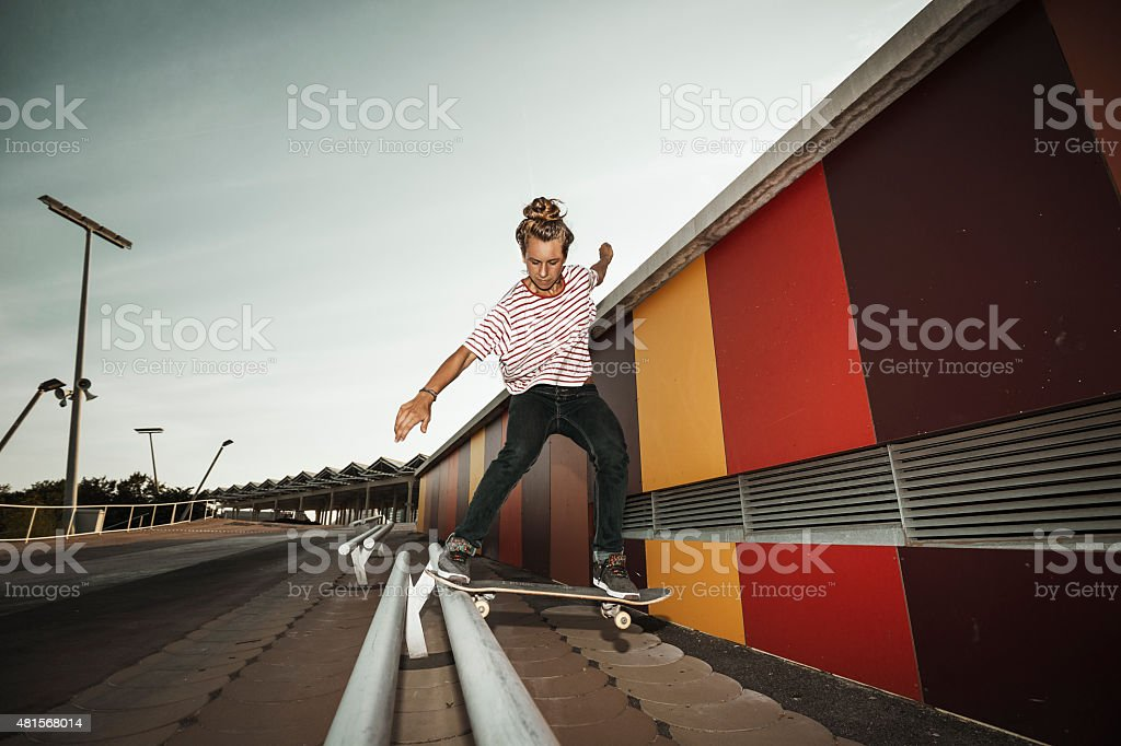 Young female skateboarder grinding stock photo