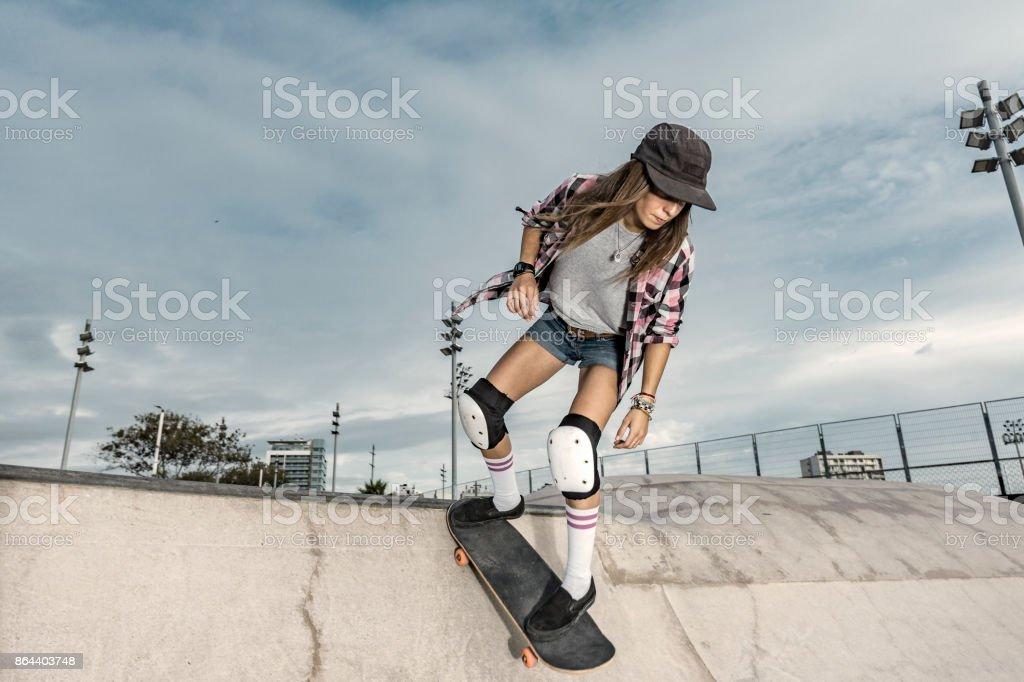 Young female skateboarder in skateboard park stock photo