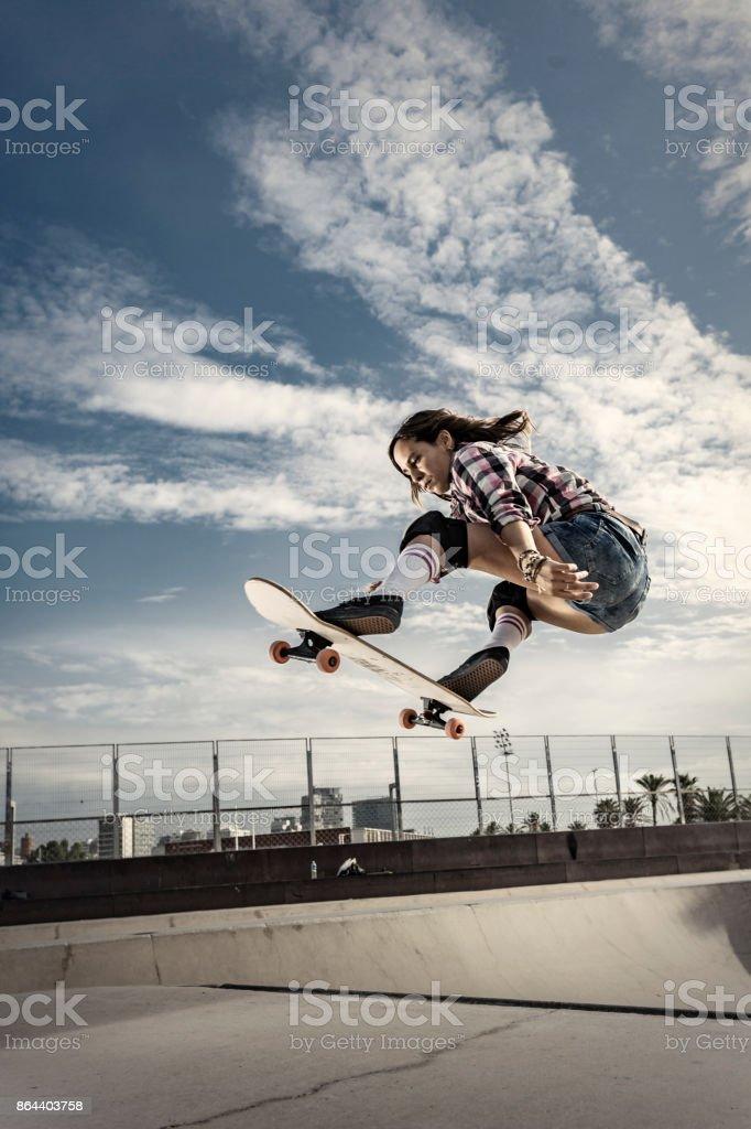 Young female skateboarder jumping in skateboard park in Barcelona Catalonia Spain stock photo