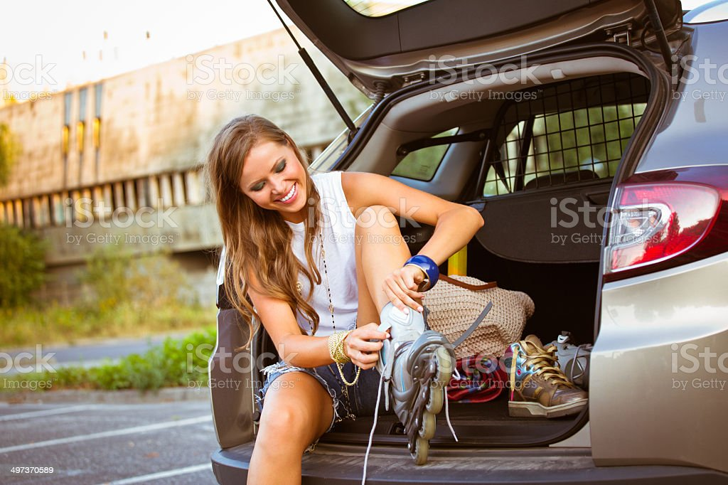Young female skater Young female skater sitting in a back of van and ties her rollers. 20-24 Years Stock Photo