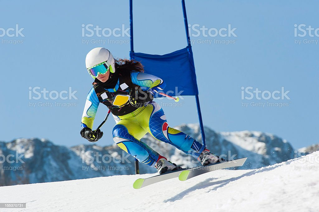 Young female skier jumping during the downhill race stock photo