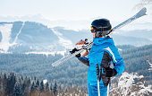 Young female skier with skiing equipment enjoying at winter ski resort in beautiful sunny day copyspace happiness positivity vacation travelling Bukovel