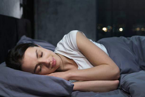 Young female sleeping peacefully in her bedroom at night, relaxing Young female sleeping peacefully in her bedroom at night, relaxing positive emotion stock pictures, royalty-free photos & images