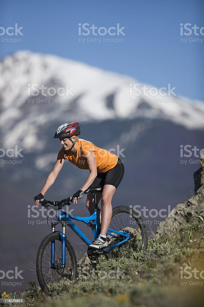 Young Female Smiling And Riding Bicycle Against Snow-Covered Mountains royalty-free stock photo