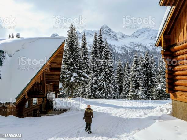 Young female snowshoer walking in between two wood cabins during the picture id1132903831?b=1&k=6&m=1132903831&s=612x612&h=amodubopgk6ua2fewtestodkx8tyb5pnqe0o1pcklmy=