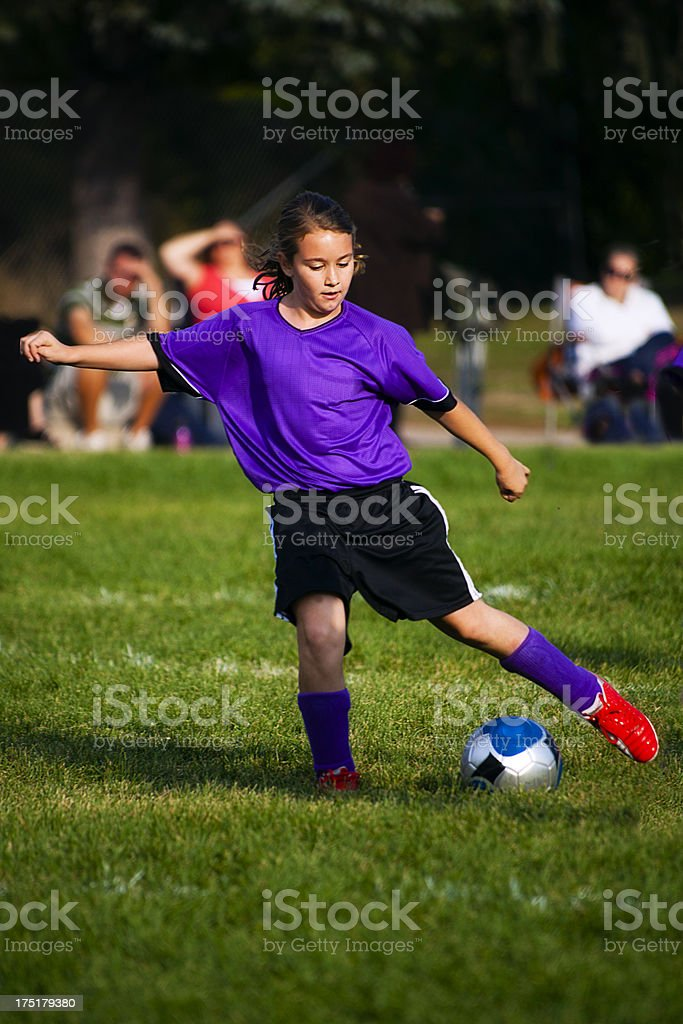 Young Female Soccer Player Reaches for Ball with Foot stock photo