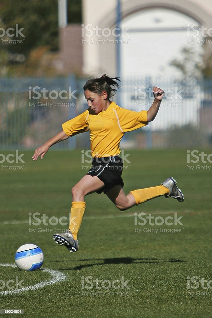Young Female Soccer Player Soars in Flying Power Hit royalty-free stock photo