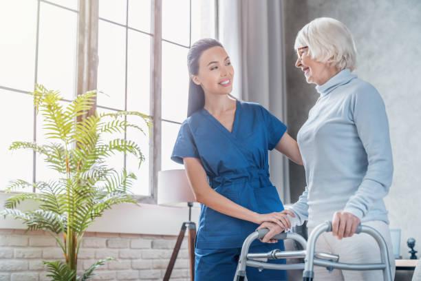 自宅で歩行者と一緒に歩くシニア女性を助ける若い女性ソーシャルワーカー - 介護士 ストックフォトと画像