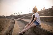 日没時にビーチでリラックスした若い女性のソロ観光客