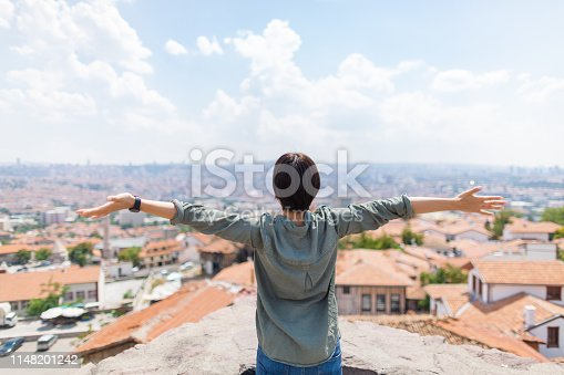 A young female solo traveler is raising her arms while looking at city.
