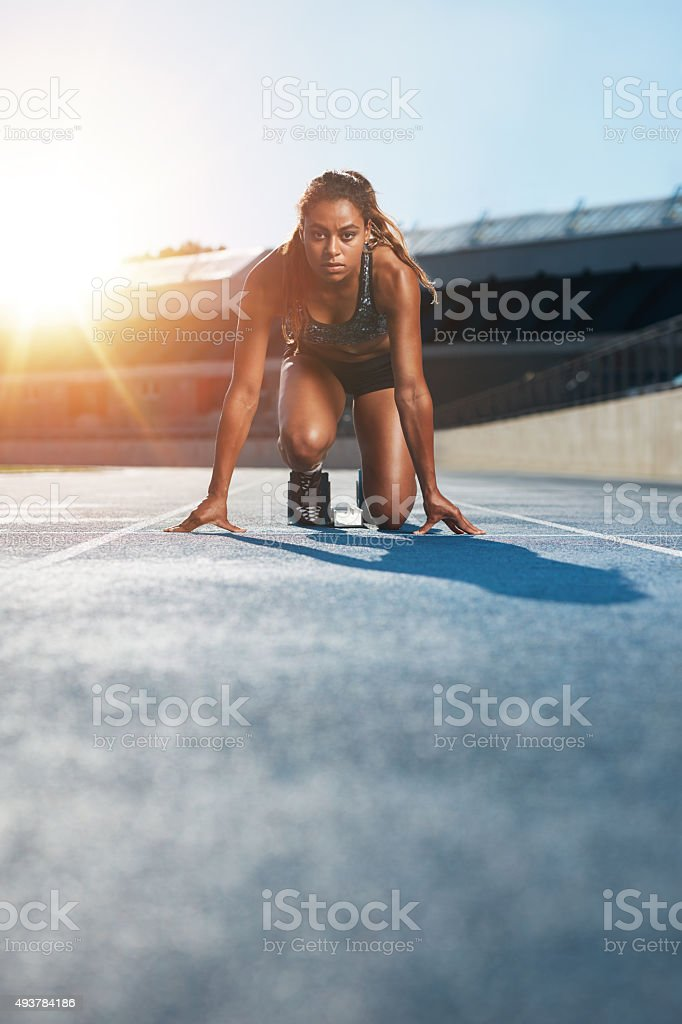 Young female sprinter in start position on racetrack Vertical shot of young female sprinter taking ready to start position facing the camera.  Woman athlete in starting blocks with sun flare. 2015 Stock Photo