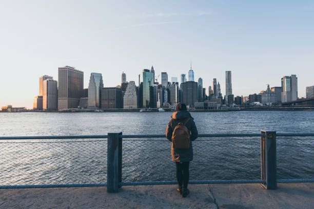Young Female Standing in Front of Manhattan Young Female Standing in Front of Manhattan lower manhattan stock pictures, royalty-free photos & images