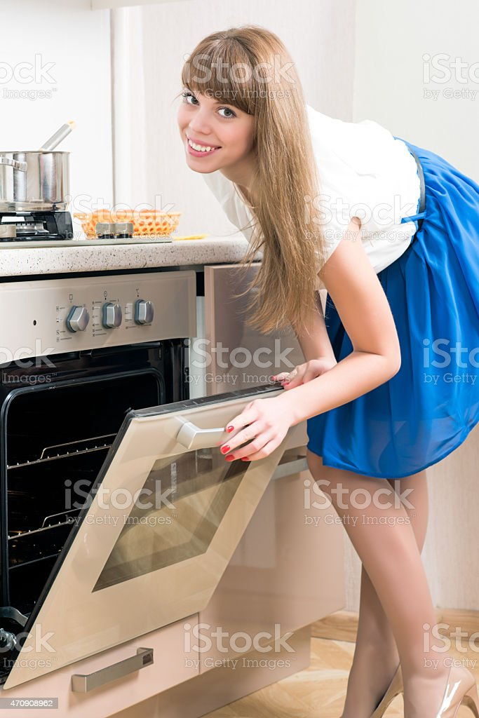 Young female standing in front of the opened oven stock photo