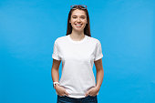 istock Young female standing with hands in pockets, wearing blank white t-shirt with copy space, isolated on blue background 1153003804