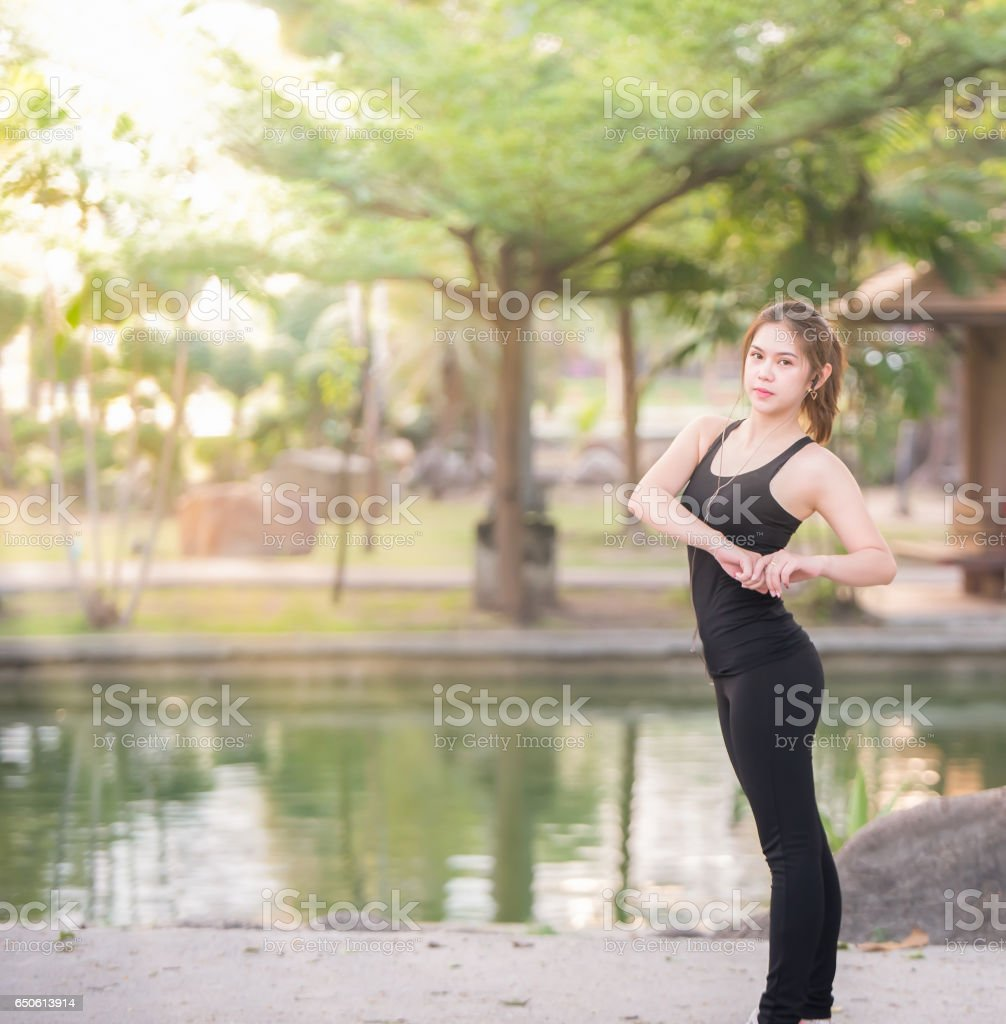 Young female stretching before fitness training session at the park. Healthy young woman warming up outdoors. She is stretching her arms and looking away stock photo