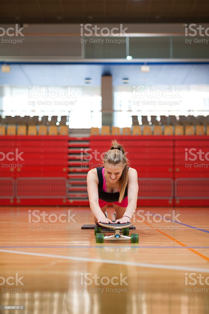 Young Female Stretching Exercises With Skateboard Front View royalty-free stock photo