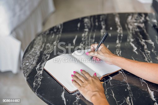 istock Young female student doing homework 908644482