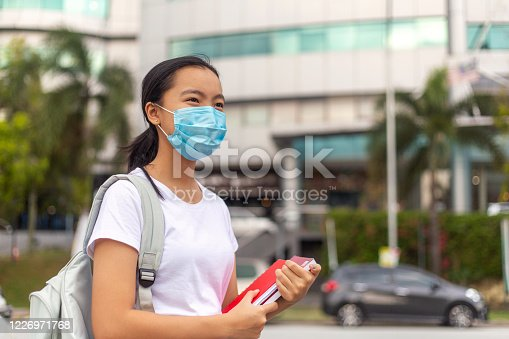 Virus Protection: Outdoor Portrait of an young Asian teenager on the way to school, Wearing a Protective Face Mask