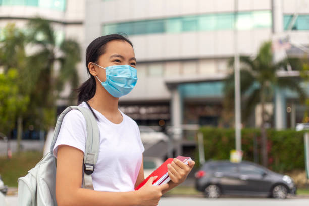 young female student going to school wearing protective facemask - pics for cool girl stock pictures, royalty-free photos & images