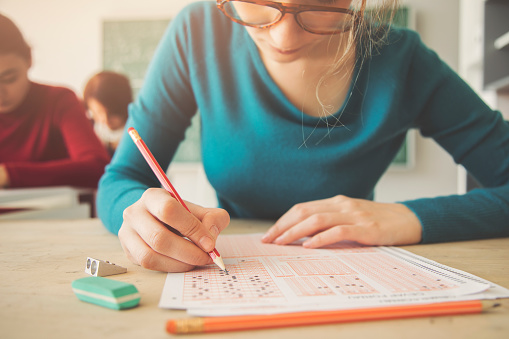 istock Young female student having examination in classroom 944043470