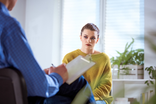 Young Female Student Listening To Therapist Stock Photo - Download Image Now