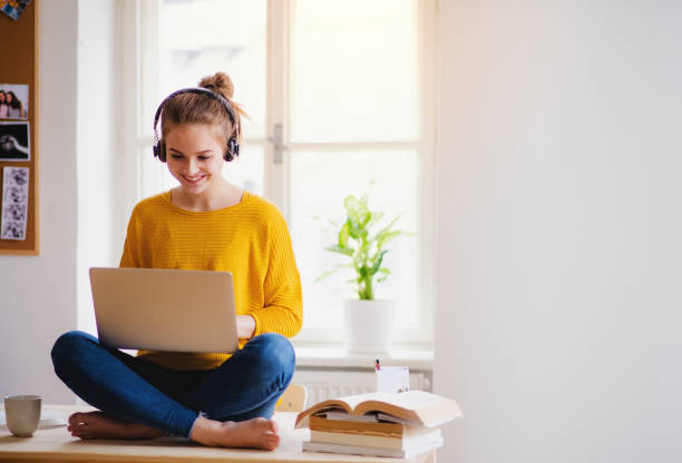 A young female student sitting at the table, using headphones when studying. stock photo