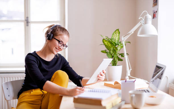 A young female student sitting at the table, using tablet when studying. A young happy college female student sitting at the table at home, using tablet and headphones when studying. listening stock pictures, royalty-free photos & images