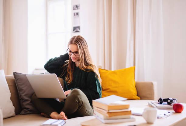 一個年輕的女學生坐在坐在一個女學生,在學習時使用筆記本電腦。 - 少女 個照片及圖片檔