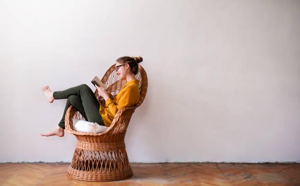 Eine junge Studentin, die auf dem Korbstuhl sitzt und liest. Kopieren Sie den Speicherplatz. – Foto