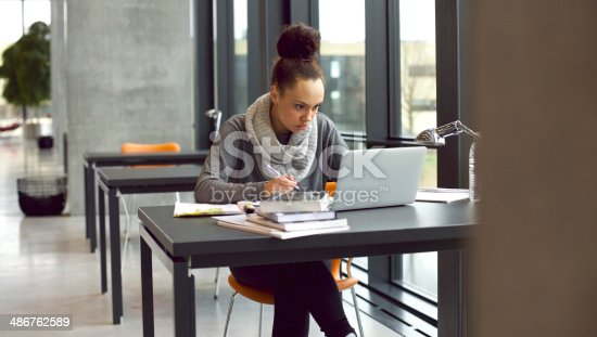 istock Young female student taking notes for her study 486762589
