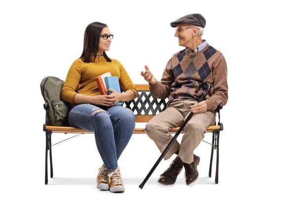 estudante fêmea novo que fala a um homem idoso em um banco - banco assento - fotografias e filmes do acervo