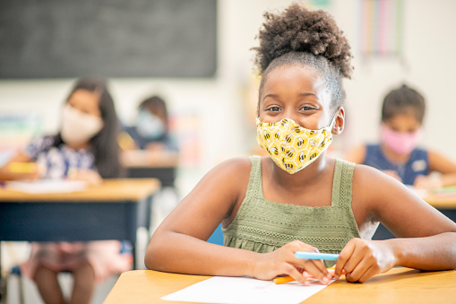 10 year old, African-American student wearing a reusable face covering while working on school work at her desk in class.