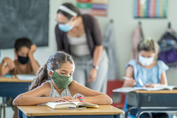 Young female student wearing a protective face mask in the classroom 12 year old girl wearing a reusable, protective face mask in classroom while working on school work at her desk. classroom stock pictures, royalty-free photos & images