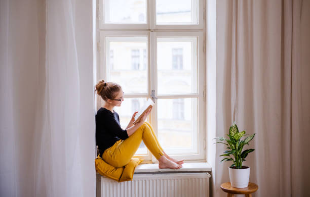 A young female student with a book sitting on window sill, studying. stock photo