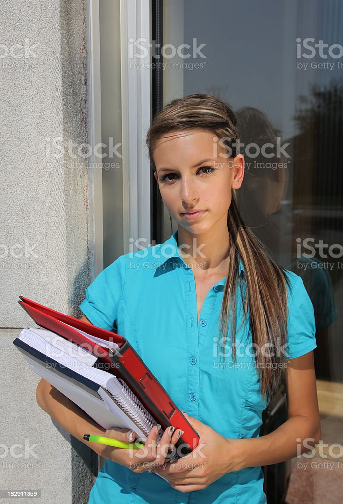 Young female student with books in front of a School stock photo