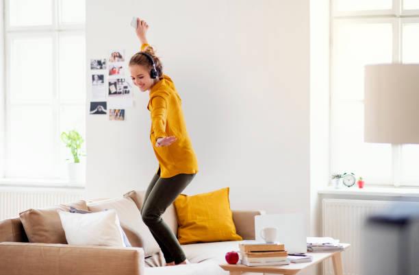 Eine junge Studentin mit Kopfhörern tanzt beim Studium auf dem Sofa. – Foto