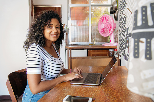 Young female student working on laptop at home