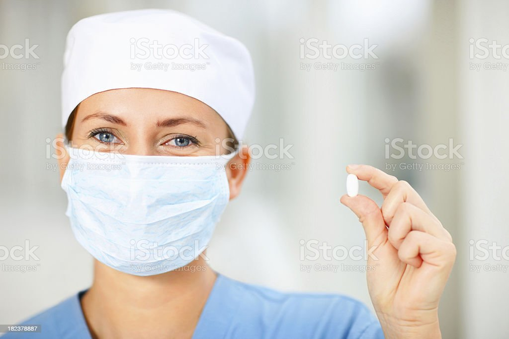 Young female surgeon holding pill royalty-free stock photo