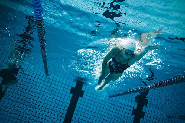 young female swimmer training in the pool - vuelta completa fotografías e imágenes de stock