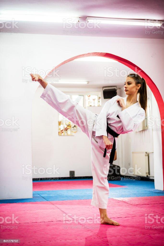 Young female taekwondo enthusiast on training, warming up stock photo