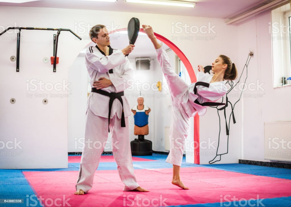 Young female taekwondo enthusiast on training, warming up stock photo