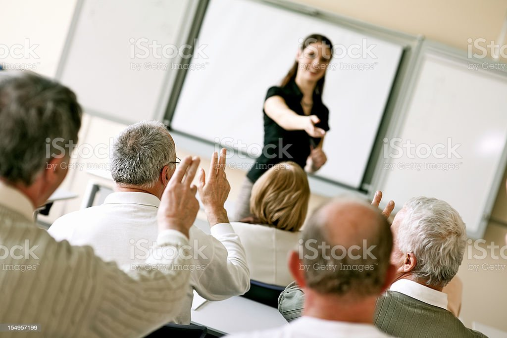 Young female teacher and adult learners in seminar stock photo
