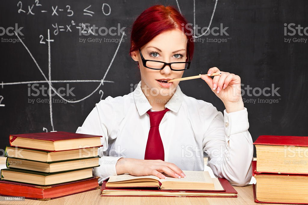 Young female teacher at desk biting pen provocatively royalty-free stock photo
