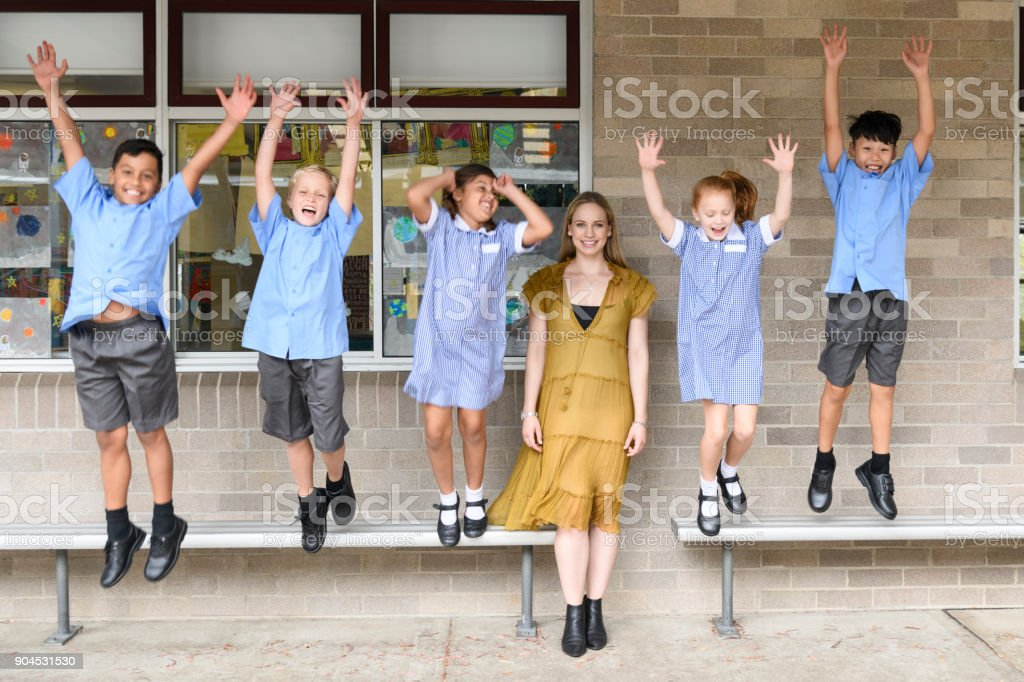 Young female teacher in front of five children jumping and shouting stock photo