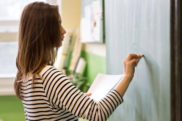 young female teacher or a student writing math formula on blackboard in classroom. - formula 1 стоковые фото и изображения
