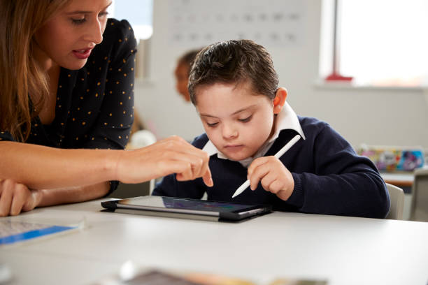young female teacher working with a down syndrome schoolboy sitting at desk using a tablet computer in a primary school classroom, front view, close up - handicapped imagens e fotografias de stock