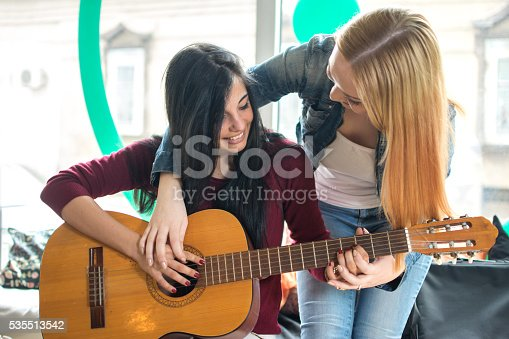 1155122702 istock photo Young female teaching her girlfriend to play guitar. 535513542